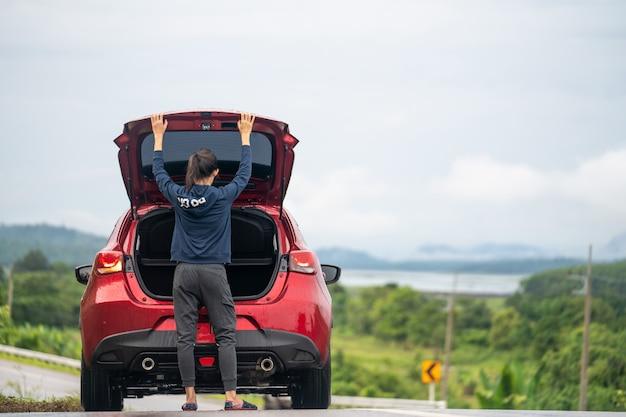 Een reismeisje en auto op de weg
