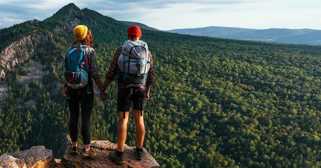 Een reizend stel in de bergen. een man en een vrouw op de achtergrond van een berg, een panorama. de berg beklimmen. wandelen in de bergen. actieve recreatie in het nationale park. ruimte kopiëren