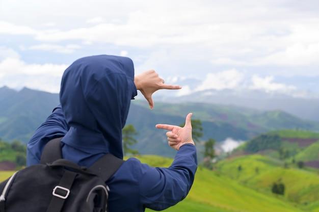 Een reizende man die geniet van en ontspant over het prachtige groene uitzicht op de bergen in het regenseizoen, tropisch klimaat.