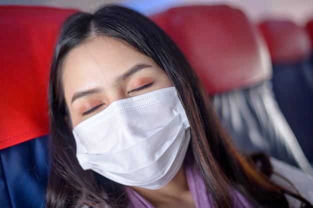 Een reizende vrouw draagt een beschermend masker aan boord van het vliegtuig dat onder de covid-19 pandemie reist
