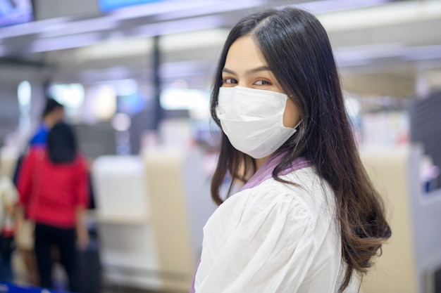 Een reizende vrouw draagt een beschermend masker op de internationale luchthaven, die reist onder de covid-19 pandemie
