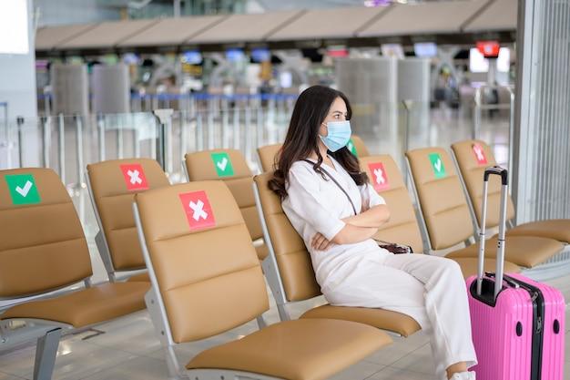 Een reizende vrouw draagt een beschermend masker op de internationale luchthaven, reist onder covid-19 pandemie, veiligheidsreizen, sociaal afstandsprotocol, nieuw normaal reisconcept.