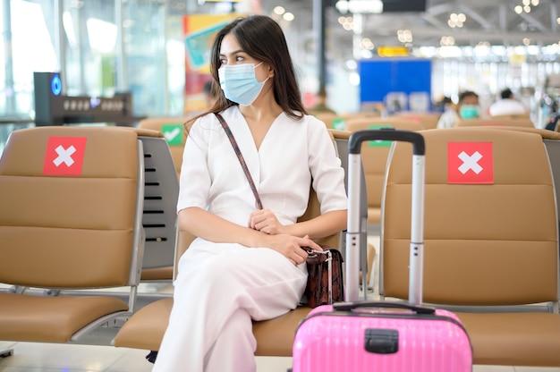 Een reizende vrouw draagt een beschermend masker op de internationale luchthaven, reist onder covid-19 pandemie,