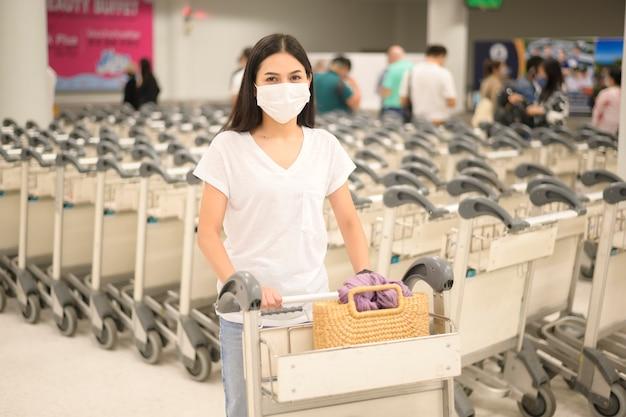Een reizende vrouw draagt een beschermend masker op de luchthaven met bagage op trolley, reist onder covid-19 pandemie, veiligheidsreizen, sociaal afstandsprotocol, nieuw normaal reisconcept
