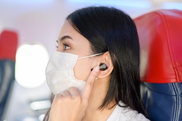 Een reizende vrouw met een beschermend masker aan boord in het vliegtuig met behulp van een koptelefoon, reizen onder covid-19 pandemie, veiligheidsreizen, sociaal afstandsprotocol, nieuw normaal reisconcept