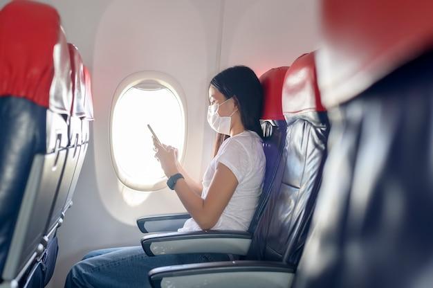 Een reizende vrouw met een beschermend masker aan boord in het vliegtuig met behulp van smartphone, reizen onder covid-19 pandemie, veiligheidsreizen, sociaal afstandsprotocol, nieuw normaal reisconcept