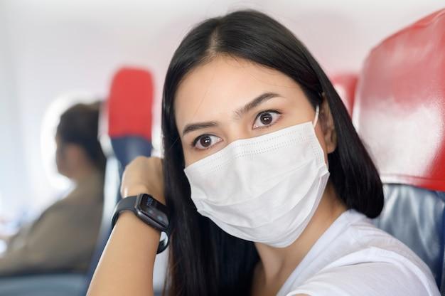 Een reizende vrouw met een beschermend masker aan boord in het vliegtuig met behulp van smartwatch, reizen onder covid-19 pandemie, veiligheidsreizen, sociaal afstandsprotocol, nieuw normaal reisconcept