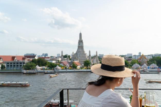 Een reiziger die in wat arun ratchawararam ratchawaramahawihan-tempel in bangkok, thailand reist