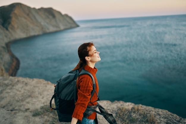 Een reiziger in de bergen gebaart met haar handen in de buurt van de zee bij zonsondergang herfst landschap