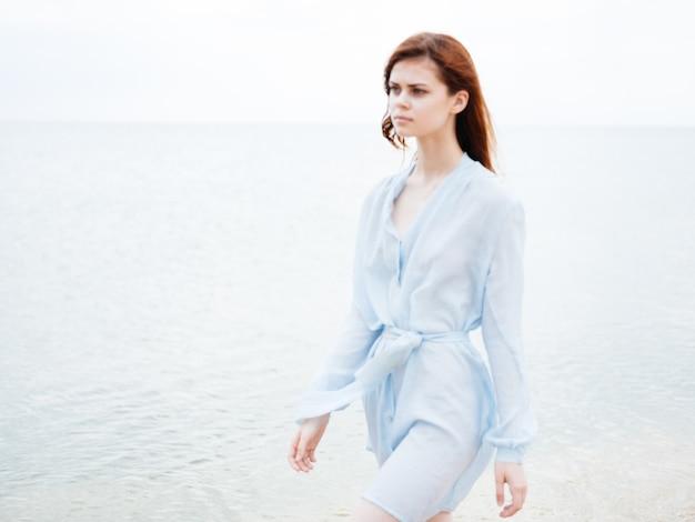 Een reiziger in een blauwe jurk rent langs de kust op het strand