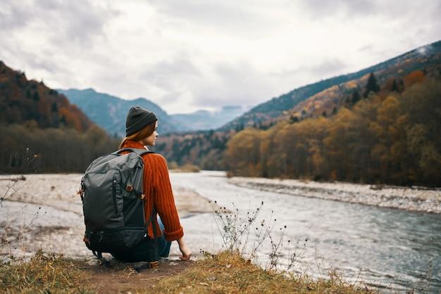 Een reiziger in een jasje met een rugzak op haar rug hoed bergen landschap rivier