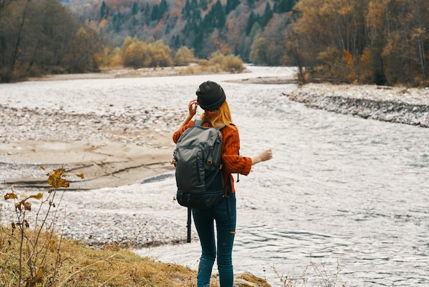 Een reiziger in een sweaterhoed met rugzak gebaart met haar handen en ontspant zich op de oever van de rivier