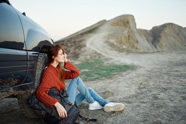 Een reiziger in een trui en spijkerbroek zit op de grond met een rugzak in haar hand bij een auto in de