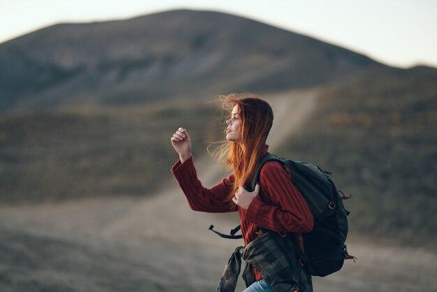 Een reiziger in een trui met een rugzak op haar rug kijkt naar buiten in de bergen