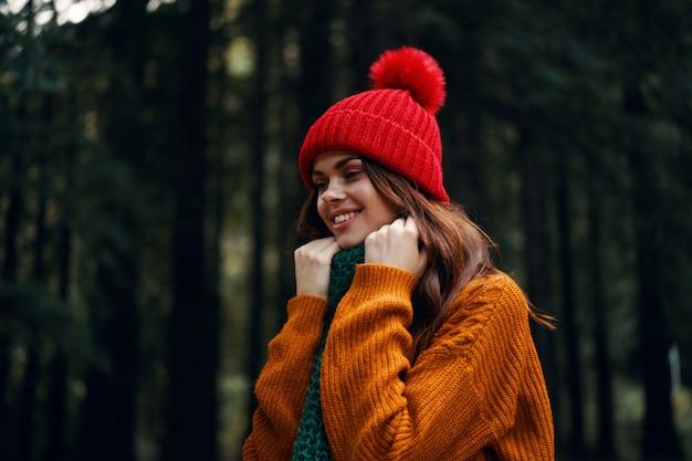 Een reiziger in het bos in een rode hoed en een oranje trui