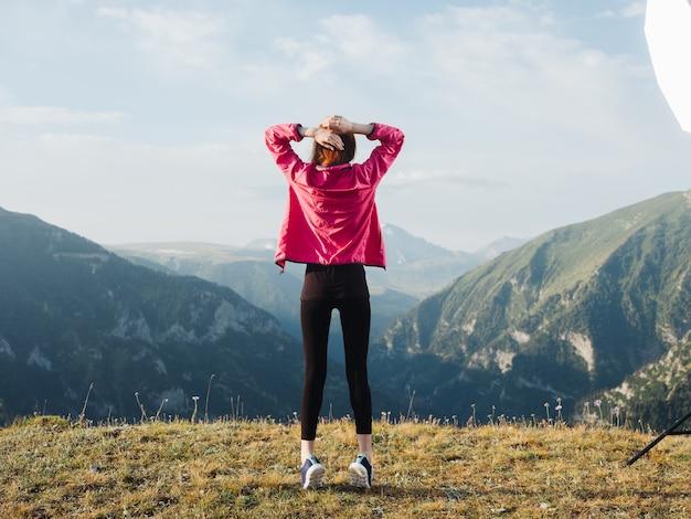 Een reiziger in legging, gympen en jasje rust in de bergen in de natuur