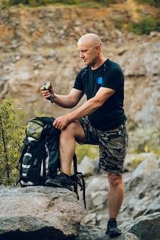 Een reiziger kijkt naar het kompas in zijn hand en houdt een rugzak naast zich