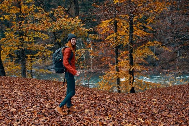 Een reiziger met een rugzak loopt in de herfst in het park in de natuur bij de rivier