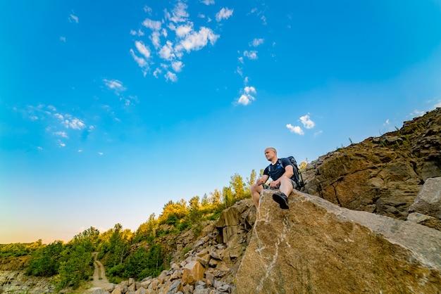 Een reiziger met een rugzak zit op een grote steen met een scherp uiteinde