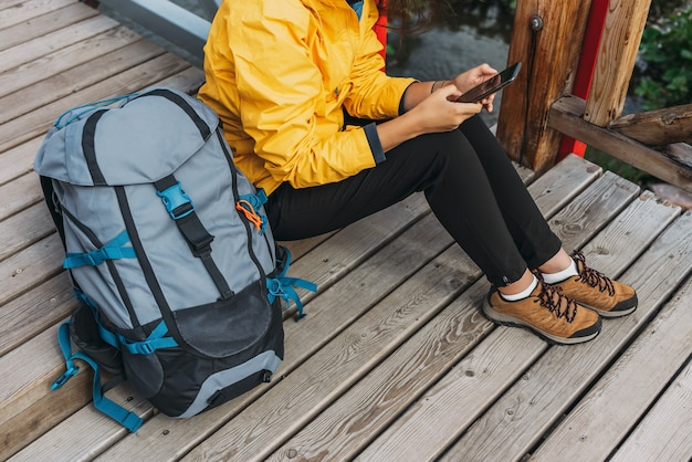 Een reiziger met een telefoon, close-up. een toeristenmeisje in een geel jasje met een rugzak houdt een telefoon in haar handen. wandelende vrouw met behulp van slimme telefoon, reizen en actieve levensstijl concept. ruimte kopiëren