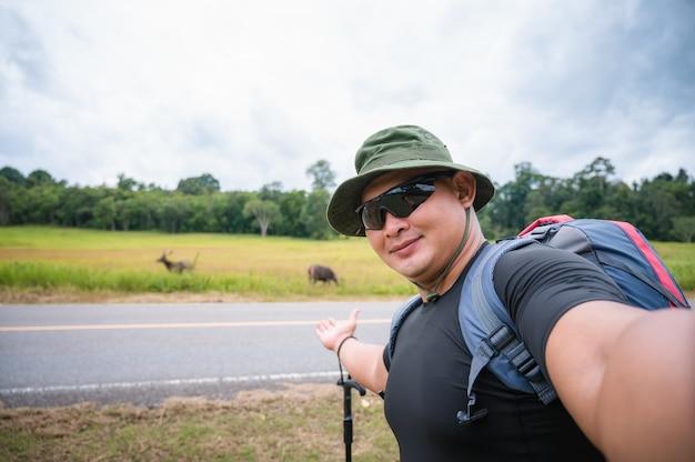 Een reiziger met een wandelrugzak kijkt naar herten die in het bos grazen. toeristen nemen een selfie met herten die grazen in een tropisch bos in khao yai national park, thailand.