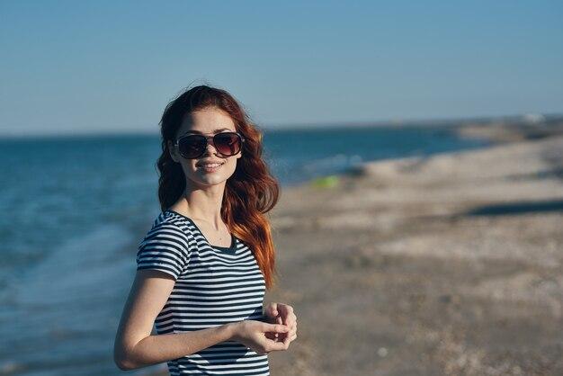 Een reiziger met zonnebril en t-shirt rust op het strand bij de zee in de bergen