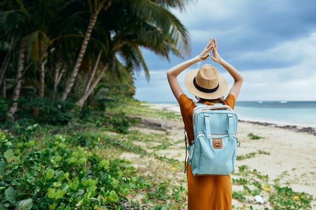 Een reiziger op het eiland met opgeheven armen in de buurt van de oceaan