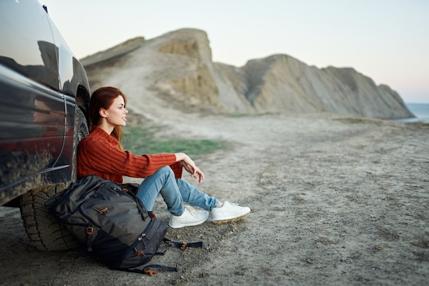 Een reiziger zit naast een auto in de bergen in de natuur en bewondert het landschap bij zonsondergang Premium Foto