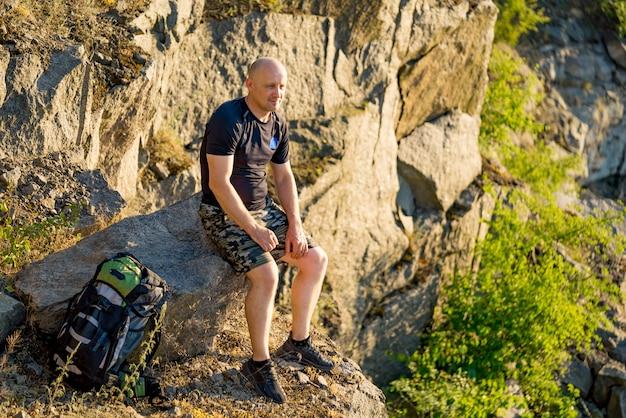 Een reiziger zit op een steen met een rugzak in de buurt van zijn benen