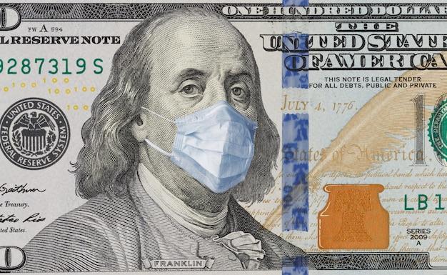 Een rekening van 100 met een medisch masker op benjamin franklin van de covid-19