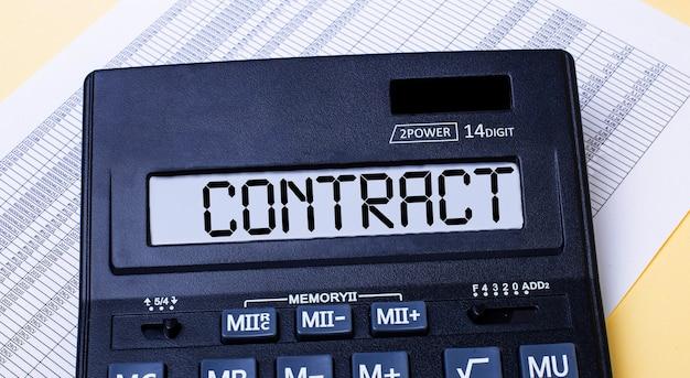 Een rekenmachine met het label contract staat op de tafel naast het rapport. financieel concept