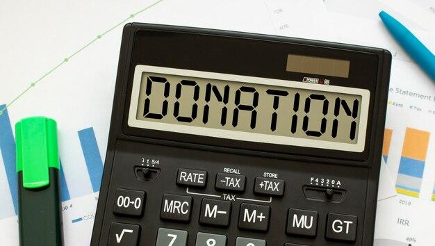 Een rekenmachine met het label donation ligt op financiële documenten op kantoor