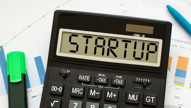 Een rekenmachine met het label startup ligt op financiële documenten op kantoor. bedrijfsconcept