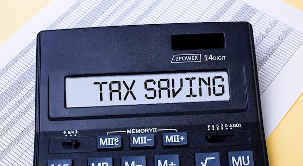 Een rekenmachine met het label tax saving staat op de tafel naast het rapport. financieel concept