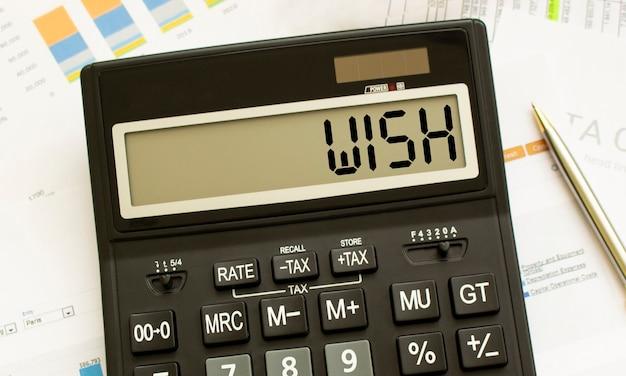 Een rekenmachine met het label wish ligt op financiële documenten op kantoor. bedrijfsconcept.