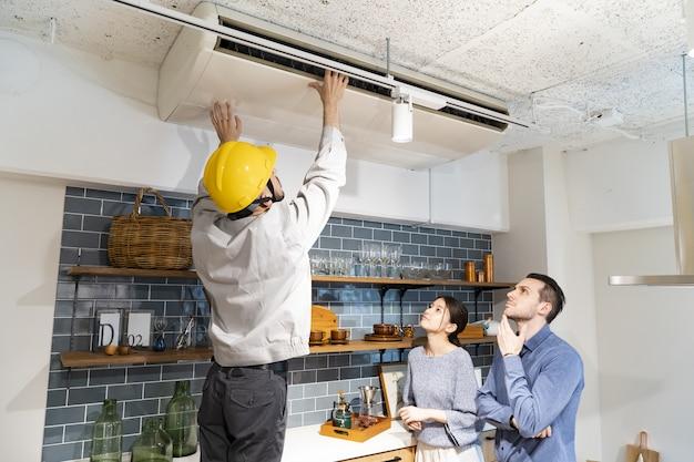 Een reparateur die de airconditioner controleert