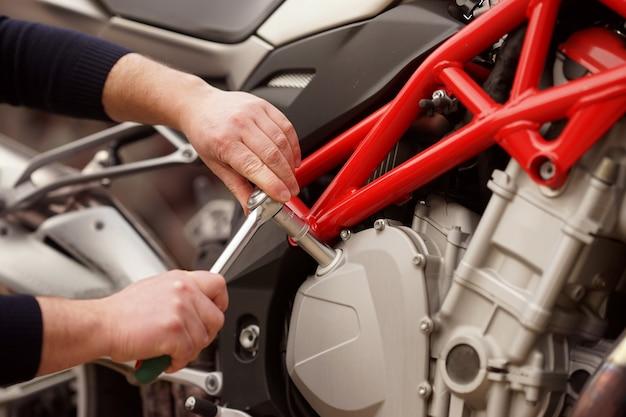 Een reparateur repareert een detail van een motorfiets op een serviceplaats