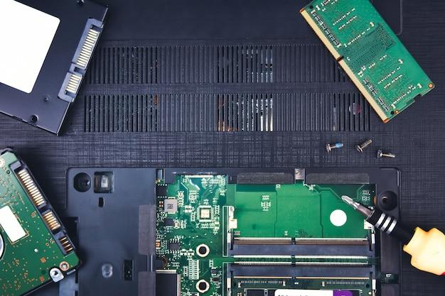 Een reparatielaptopcomputer met een harde schijf en ram op de achtergrond (random access memory)