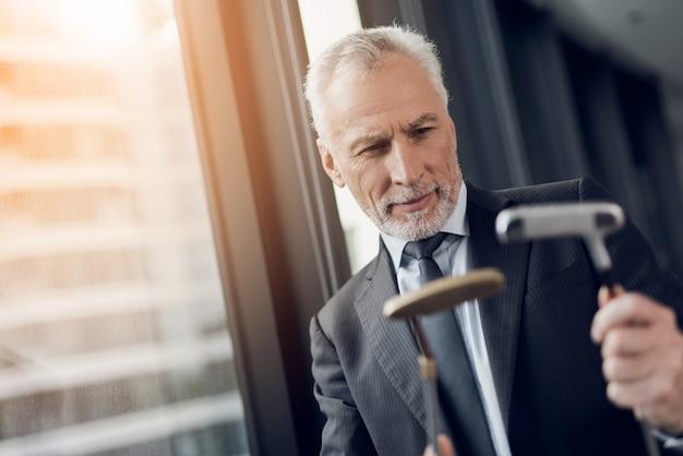 Een respectabele oudere man een minigolf spelen op kantoor