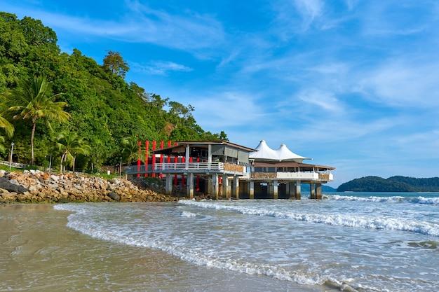 Een restaurantgebouw aan de oceaan van een tropisch eiland.