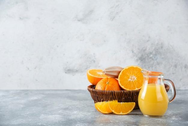 Een rieten doos vol sappig oranje fruit op stenen tafel.