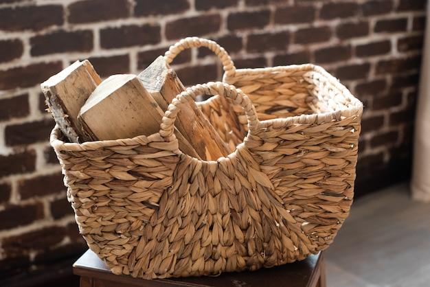 Een rieten mand gemaakt van papierranken gevuld met brandhout. recycling, eco, natuurlijke materialen, milieuvriendelijk. boho-stijl, rustiek, gezellig.