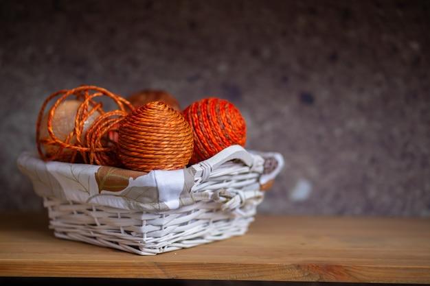 Een rieten mand met daarin gevouwen oranje bollen draad of touw.