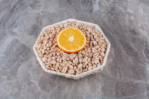 Een rieten mand met gezond gepofte rijstontbijtgranen met een schijfje sinaasappelfruit.