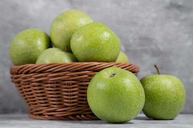 Een rieten mand met verse groene appels op steen