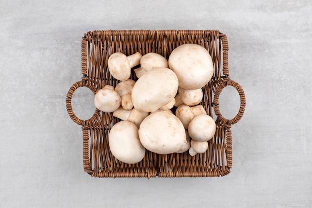 Een rieten mand met verse witte champignons op stenen tafel.