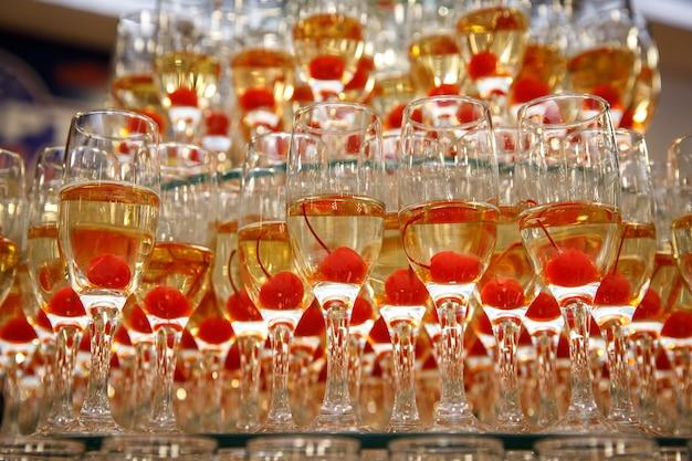 Een rij glazen met champagne en kersen binnen bij het evenement.
