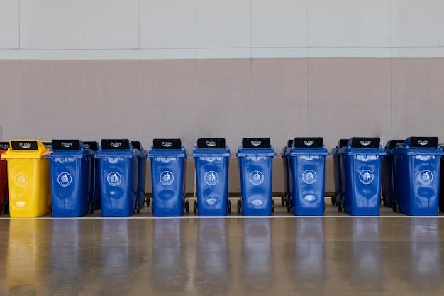 Een rij grote donkerblauwe industriële plastic afvalcontainers.