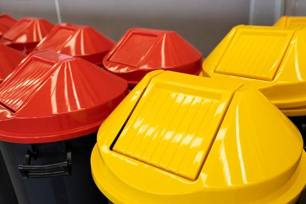 Een rij grote felgele en rode plastic afvalcontainers.