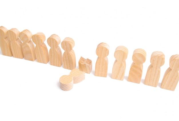Een rij houten mensen en een gebroken figuur van een persoon onder hen.